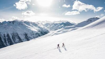 People hike up snow-covered mountains.