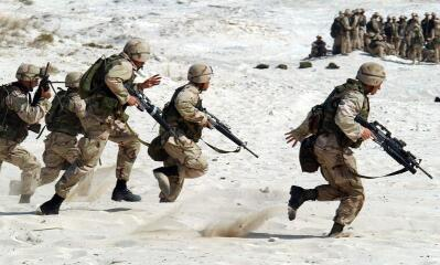 Soldiers run in the sand.