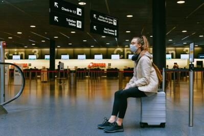 A woman sitting on her luggage at the airport