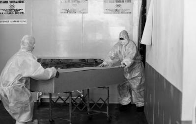 Two people in hazmat suits wheel out a coffin.