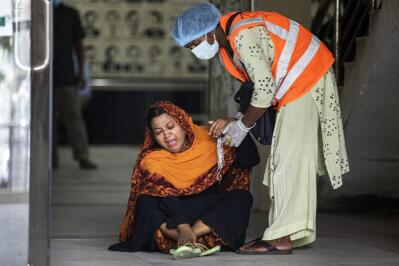 A health care worker assisting a woman weeping on the floor