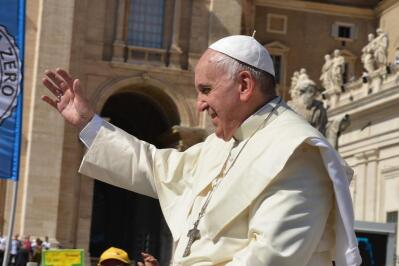 Pope Francis waving his hand from a Vatican balcony.