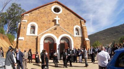 People gather around a church.