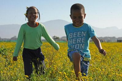 Two children running through a field of yellow flowers.